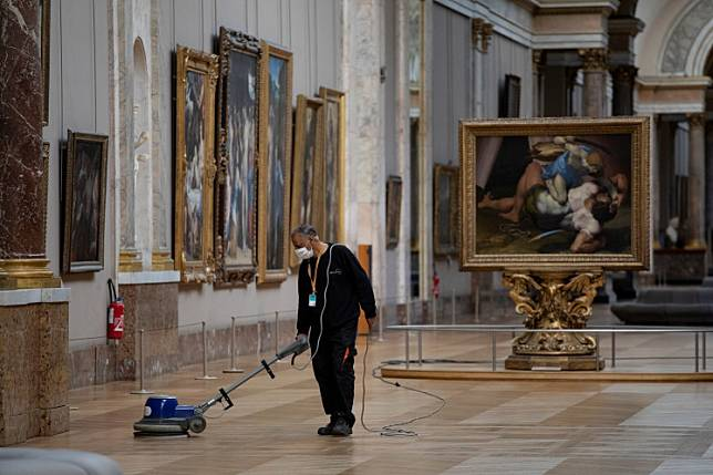 A picture taken on June 23, 2020 shows an employee cleaning the floor of a room of the Musee du Louvre in Paris.