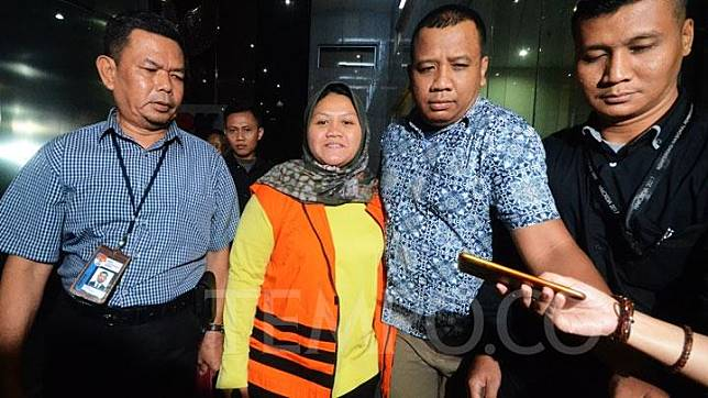 Bupati Bekasi Neneng Hasanah Yasin tersenyum saat keluar dari gedung KPK dengan mengenakan rompi tahanan pada Selasa, 16 Oktober 2018. Neneng resmi ditahan KPK setelah menjalani pemeriksaan pasca-ditetapkan sebagai tersangka dalam kasus dugaan suap perizinan proyek Meikarta. TEMPO/Imam Sukamto