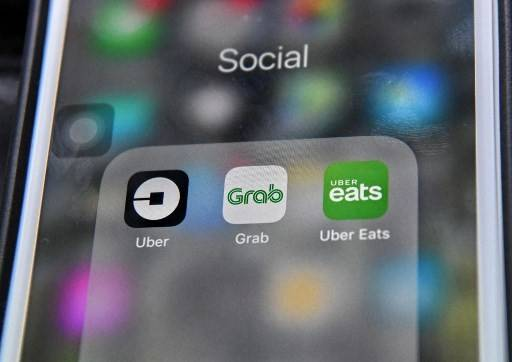 This photo illustration taken on March 26, 2018 shows the Grab and Uber booking application seen on a smart phone in Singapore. Singapore-based ride-hailing firm Grab announced on March 26 it has bought US rival Uber's business in Southeast Asia, ending a fierce battle for market share in the region.
