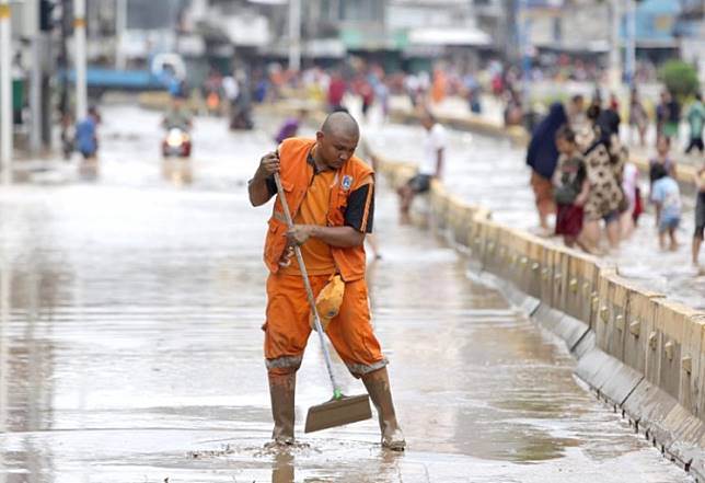 A worker from the Jakarta Public Order Agency cleans up mud residue on Jl. Jatinegara Barat in East Jakarta on Jan. 2. The Indonesian capital and surrounding areas marked the start of the new year with widespread flooding.