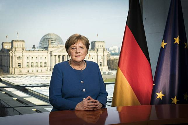 This Handout photo made available by the German government's press office shows German Chancellor Angela Merkel posing for a photo at the recording of a TV address to the nation on the spread of the new coronavirus COVID-19 at the Chancellery, with a view of the Reichstag, the building housing the lower house of parliament, through the window in Berlin on March 18, 2020. Germany will plough 130 billion euros ($146 billion) into a stimulus package to kick-start an economy severely hit by the coronavirus pandemic, Merkel said Wednesday.