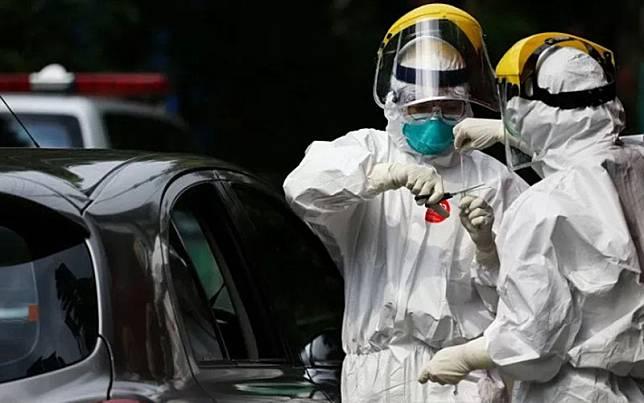 Petugas medis mengambil sampel spesimen saat swab test virus corona Covid-19 secara drive thru di halaman Laboratorium Kesehataan Daerah (Labkesdan) Kota Tangerang, Banten, Senin (6/4/2020)./Antara-Fauzan