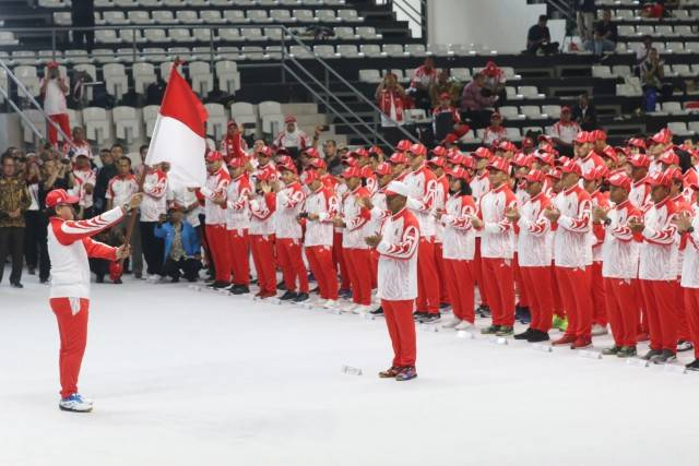 Team Indonesia chief contingent Harry Warganegara (left) raises the country's flag during the team's send-off in Jakarta, prior to their departure to the 30th Southeast Asian (SEA) Games in the Philippines.