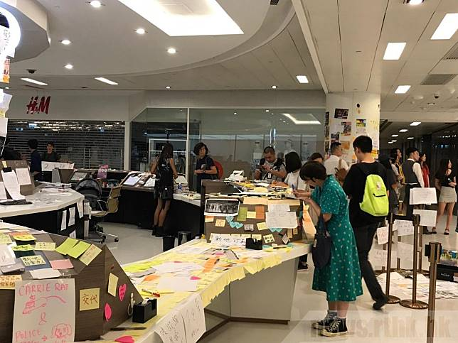 市民在客戶服務中心及商場3樓詢問處後方的柱上,貼上便條紙。(黃貝紋攝)