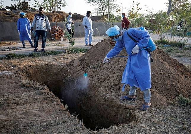 A municipal worker wearing a protective suit sprays disinfectant solution in a grave before the burial of a woman who died due to COVID-19, in Ahmedabad, India, March 28, 2020. A Kashmiri villager faked his death and travelled more than a hundred miles in an ambulance with four others in a desperate bid to circumvent India's virus lockdown and return home.