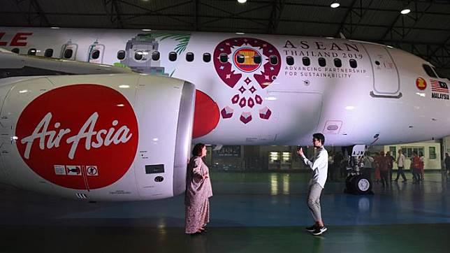 Tamu undangan berpose di samping armada AirAsia Airbus A320 yang menggunakan corak