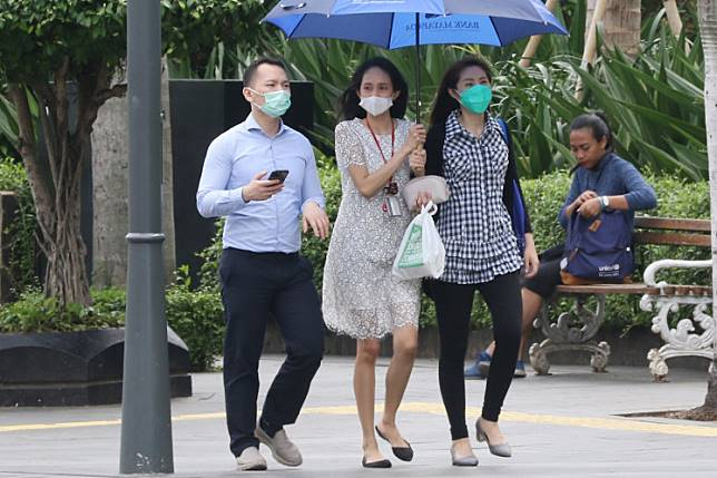 Precaution: People wearing masks walk along Jl. MH Thamrin, Central Jakarta, on Thursday. Although Indonesia has not reported any infections of the new coronavirus on its soil, people have rushed to stores to buy masks to protect themselves.