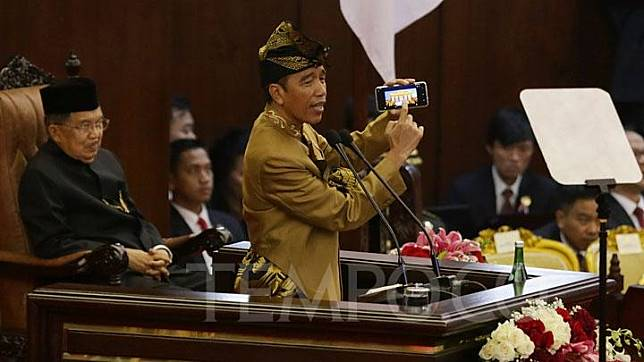 Presiden Jokowi menunjukkan gambar pada telepon seluler saat berpidato Sidang Bersama DPD dan DPR di Kompleks Parlemen, Senayan, Jakarta, Jumat, 16 Agustus 2019.  TEMPO/M Taufan Rengganis