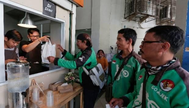 Pengemudi Go-Jek mengantre saat mereka menunggu pesanan mereka di warung kopi di Pasar Santa di Jakarta, 13 Juli 2017. Go-Jek, layanan sepeda motor yang menawarkan beragam jasa semuanya dari antar makanan, bahan makanan, jasa membersihkan rumah dan penata melalui aplikasi ponsel pintar. REUTERS/Beawiharta
