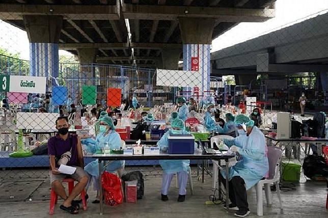 Orang-orang menerima vaksin Covid-19 dari Sinovac setelah ratusan penduduk di distrik tersebut dinyatakan positif mengidap penyakit virus corona di Bangkok, Thailand, 7 April 2021. [REUTERS / Athit Perawongmetha]