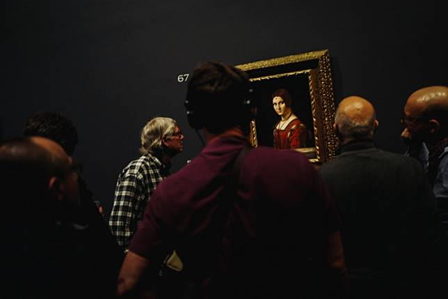 People look at the painting 'La Belle Ferronniere' (1490) by Italian Renaissance master Leonardo da Vinci during the night and free opening of the 'Leonardo da Vinci' exhibition at The Louvre Museum on February 21, 2020 in Paris.