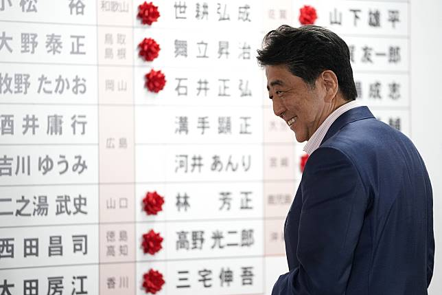 Shinzo Abe, Japan's prime minister and president of the Liberal Democratic Party (LDP), reacts after placing a red paper rose on a LDP candidate's name to indicate an election victory at the party's headquarters in Tokyo, Japan, on Sunday, July 21, 2019. Abe claimed victory in Sunday's upper house election, saying the vote showed acceptance for his plans to raise the sales tax and open debate on making the first revisions to the country's pacifist constitution. Photographer: Toru Hanai/Bloomberg