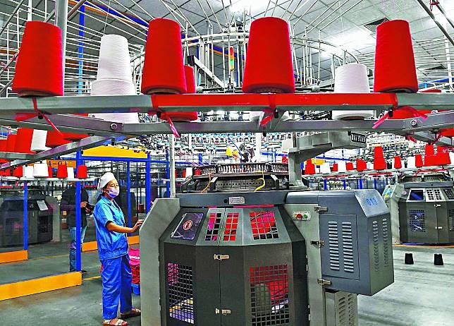 中國紡織廠實際復工率僅50%,加上各地交通管制,缺工又缺料。法新社