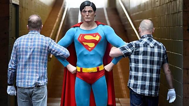 Karyawan membawa kostum Superman, yang dikenakan Christopher Reeve dalam film <i>Superman</i> pada 1978 dan 1980, yang dipamerkan di IMAX sebelum dilelang akhir bulan ini di London, Inggris, 6 September 2018. REUTERS/Toby Melville
