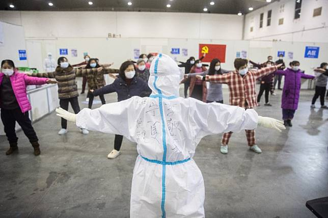 This photo taken on February 17, 2020 shows a member of the medical staff (center) leading patients who have displayed mild symptoms of the COVID-19 coronavirus in group exercises at an exhibition center converted into a hospital in Wuhan in China's central Hubei province.