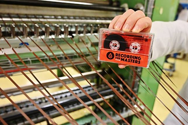 A man holds an audio cassette made with magnetic stripes in the production plant of Mulann, in Avranches, northwestern France on March 14, 2019. Mulann products magnetic stripes for magnetic cards like bank card and for audio use like vintage audio cassette.