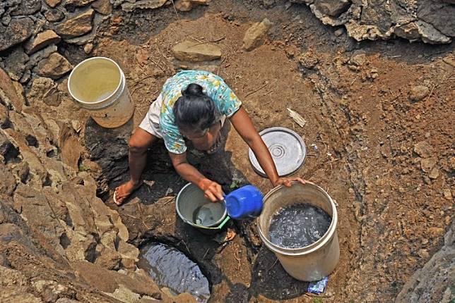 A woman collects water from the bottom of a well that has dried up in Kampung Kubang Jaya, Petir, Serang, Banten.