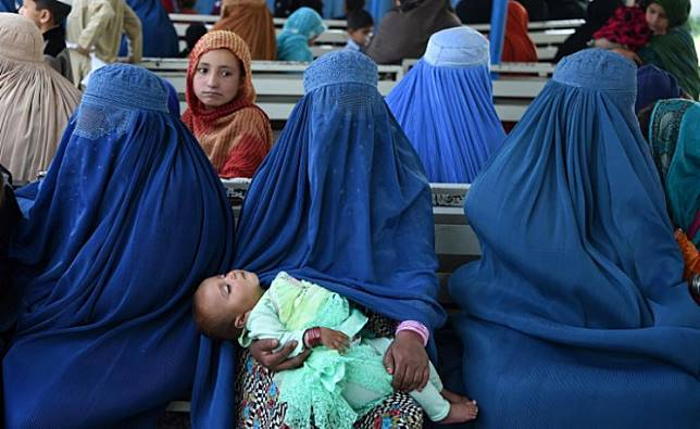 Afghan refugee women wait for their registration at the United Nations High Commissioner for Refugees (UNHCR) repatriation centre on the outskirts of Peshawar on April 11, 2017, as they prepare to return to their home country after fleeing civil war and Taliban rule.