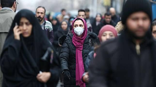 Seorang perempuan Iran berjalan mengenakan masker pelindung untuk mencegah tertular virus Corona di Grand Bazaar di Teheran, Iran, 20 Februari 2020. [WANA/Reuters]