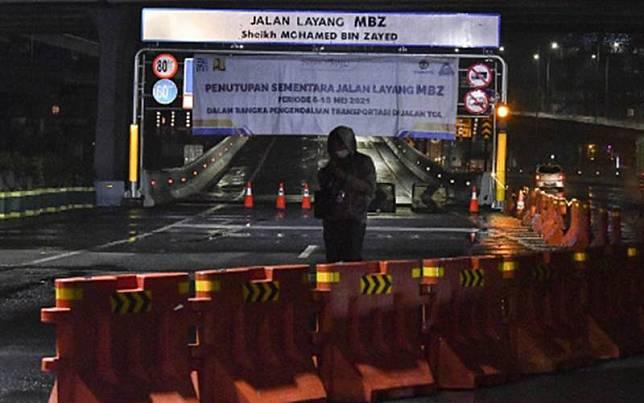 Seorang jurnalis melakukan peliputan di sekitar Tol Layang MBZ (Mohamed Bin Zayed) yang ditutup sementara di Bekasi, Jawa Barat, Kamis (6/5/2021) dini hari. Penutupan sementara Tol Layang MBZ saat masa larangan mudik tersebut untuk membatasi pergerakan masyarakat guna memutus rantai penyebaran Covid-19./Antara-Fakhri Hermansyah\\r\\n