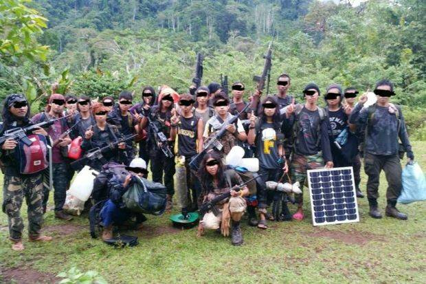 Alleged members of the Abu Sayyaf group pose with weapons.