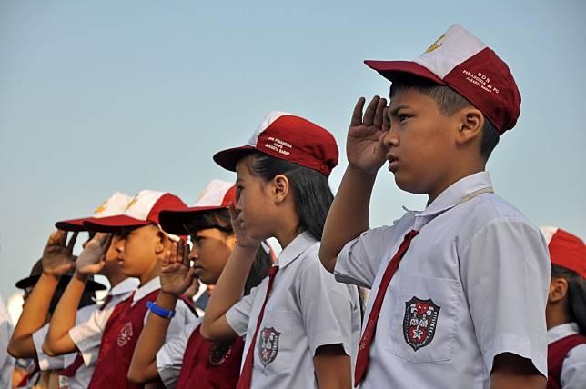 Upacara di sekolah dengan seragam merah putih.