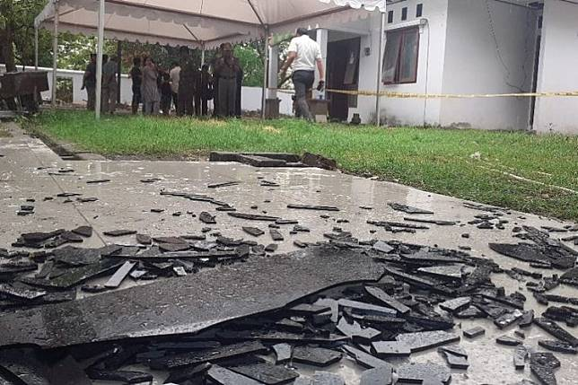 Police personnel investigate the site of a blast in the back yard of the Parepare Prosecutor's Office in Parepare, South Sulawesi on Tuesday, Nov. 19, 2019.