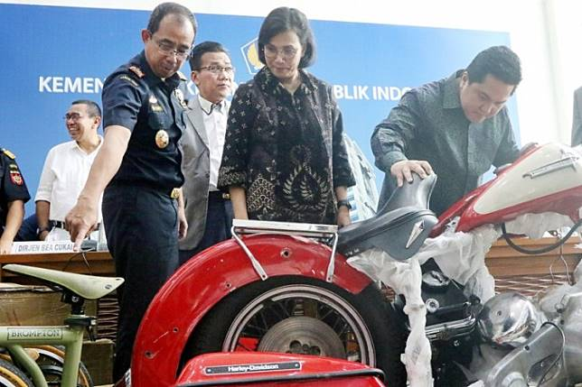 Hot wheels: State-Owned Enterprises Minister Erick Thohir (right) and Finance Minister Sri Mulyani Indrawati (center) check out a Harley-Davidson motorcycle and a Brompton bicycle allegedly smuggled into Indonesia on a Garuda Airbus A330-900 Neo aircraft, during a press conference at the Finance Ministry in Jakarta on Thursday.