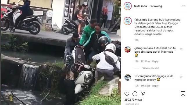 terlihat seorang wanita berupaya mengangkat skuter matik dari dalam selokan