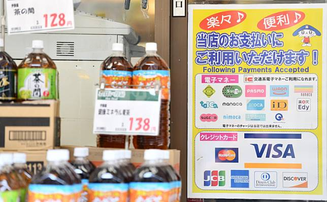 This photo taken on July 25, 2019 shows a poster offering cashless payments displayed outside a supermarket in Tokyo. Once a pioneer in cashless transactions, Japan is lagging behind as the world's biggest economies increasingly embrace electronic payments because its ageing population still prefers physical money.
