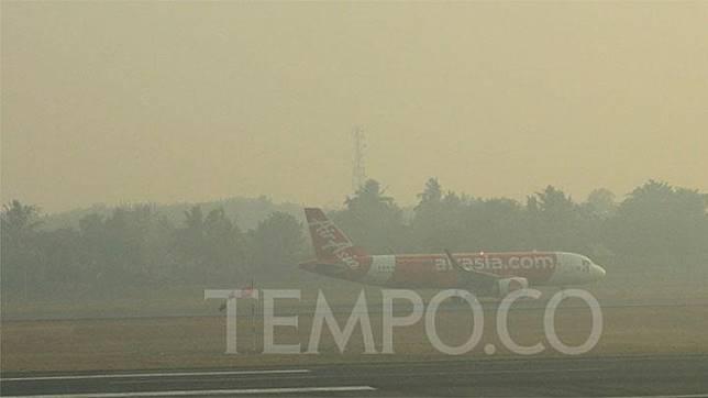 Pesawat Air Asia berhasil mendarat di bandara SMB II Palembang pekan lalu di tengah kabut asap yang menyelimuti bandara. Parliza Hendrawan