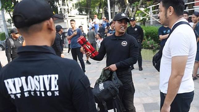Seorang anggota Unit K-9 Polri menunjukkan bom yang berhasil diendus oleh anjing pelacak di antara masyarakat yang memadati hari bebas kendaraan bermotor atau car free day (CFD) saat simulasi di Jakarta, Minggu (19/1). [ANTARA FOTO/Akbar Nugroho Gumay]