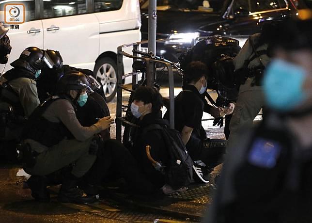 多人被制服後,雙手綁上索帶坐在路邊。(袁志豪攝)