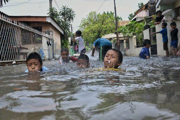 Anak-anak bermain air banjir yang melanda lingkungan rumahnya di kawasan Kebon Jeruk, Jakarta, Sabtu (18/1/2020).