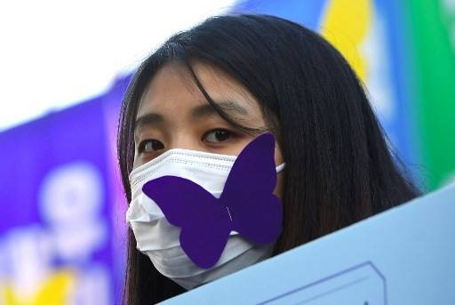 A mourner wears a face mask with a paper cutout of butterfly, symbols of sexual slavery victims, during a funeral ceremony of former South Korean