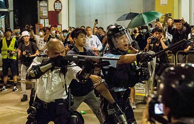 Hong Kong police officer who pointed shotgun at protesters is featured on Chinese state television's prime-time news show Xinwen Lianbo