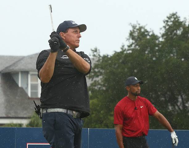 Phil Mickelson plays his shot from the first tee as Tiger Woods looks on during The Match: Champions for Charity golf round at the Medalist Golf Club.
