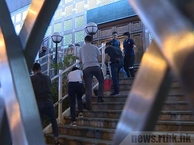 警方多人晚上持清潔用品入寺內,期間有人用毛巾清潔正門的樓梯。(袁運登攝)