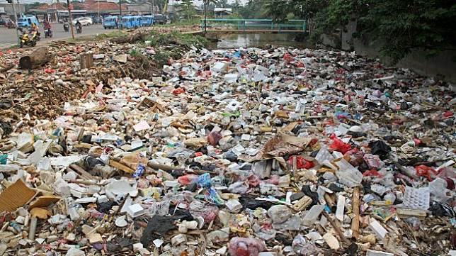 Kendaraan melintas di sekitar kali Baru yang dipenuhi sampah di Jalan Pabuaran, Bojonggede, Kabupaten Bogor, Jawa Barat, Selasa (14/5). [Suara.com/Arief Hermawan P]