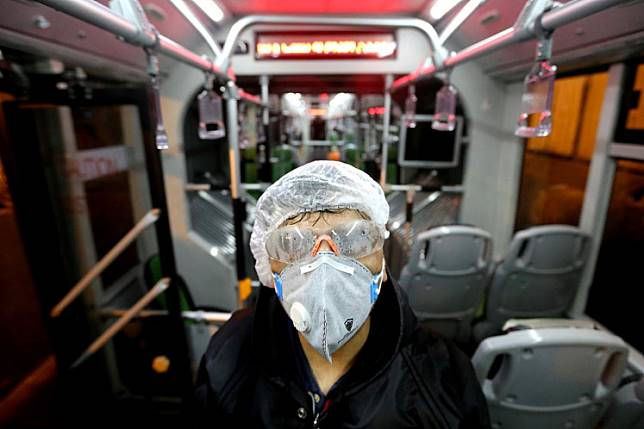 A Tehran Municipality worker cleans a bus to avoid the spread of the COVID-19 illness on Feb. 26, 2020.  Iran said Tuesday its coronavirus outbreak, the deadliest outside China, had claimed 19 lives and infected more than 100 others -- including the country's deputy health minister.