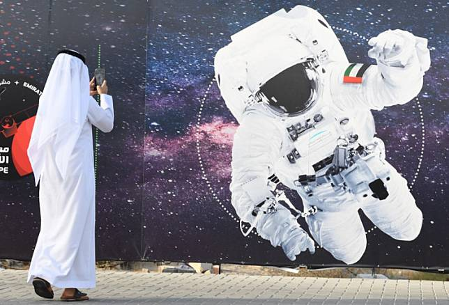 In this file photo taken on September 25, 2019 a man takes a picture of an illustration depicting an astronaut with the Emirati national flag outside Mohammed Bin Rashid Space Centre (MBRSC) in Dubai.