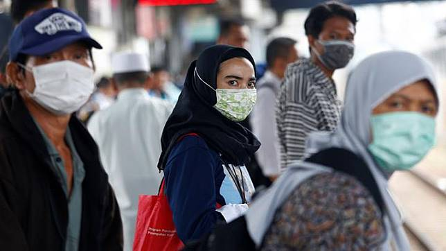 People with surgical masks look on at station Tanah Abang, following the outbreak of the coronavirus in China, in Jakarta, Indonesia February 13, 2020. Prices of face masks spiked nearly 10 times in Indonesia triggered by fears over the spread of the deadly coronavirus, as a consumer group head urged the authorities to step in to regulate the growing price. REUTERS/Ajeng Dinar Ulfiana