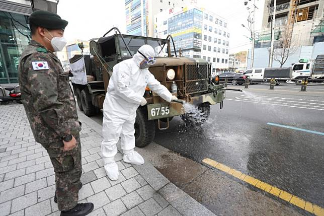 A military vehicle sprays disinfectant as part of preventive measures against the spread of the COVID-19 coronavirus, on a road in Daegu on February 27, 2020. - South Korea reported 334 new coronavirus cases on February 27, taking its total to 1,595, still the largest in the world outside China, where the disease first emerged.