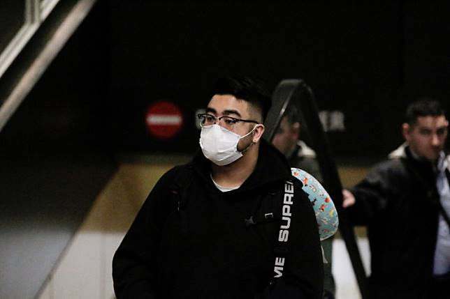 A traveler wearing a mask arrives on a direct flight from China, after a spokesman from the US Centers for Disease Control and Prevention (CDC) said a traveler from China had been the first person in the United States to be diagnosed with the Wuhan coronavirus, at Seattle-Tacoma International Airport in Washington, United States, on January 23, 2020.