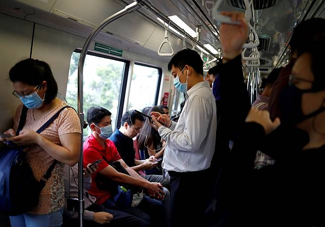 FILE PHOTO: FILE PHOTO: Commuters wearing masks in precaution of the coronavirus outbreak are pictured in a train during their morning commute in Singapore