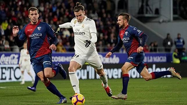 Aksi pemain Real Madrid, Gareth Bale saat menggiring bola di antara dua pemain Huesca dalam laga lanjutan Liga Spanyol di Estadio El Alcoraz, Spanyol, 9 Desember 2018. Sebuah tendangan voli yang dilepaskan Gareth Bale, berhasil mengoyak gawang Huesca saat pertandingan baru berjalan delapan menit. REUTERS/Vincent West