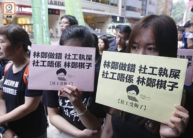 集會人士手持批評政府的標語。(何天成攝)