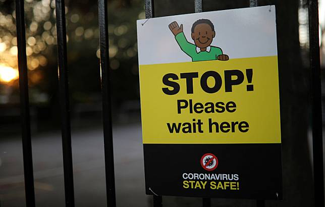 A social distancing sign is seen on the gate of a school as the spread of the COVID-19 continues in Hale, Britain, on Sunday. Health Secretary Matt Hancock said Britain was making