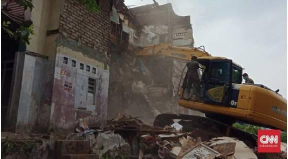 Alat berat yang dikawal petugas Satpol PP meruntuhkan bangunan rumah milik warga di RW 11, Kelurahan Tamansari, Kota Bandung untuk didirikan rumah deret, 12 Desember 2019.(CNNIndonesia/Huyogo)