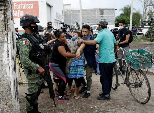 A woman reacts near the crime scene where 24 people were killed in Irapuato, Guanajuato state, Mexico, on July 1, 2020. - An armed attack at a drug rehabilitation center in Irapuato, a town in the central Mexican state of Guanajuato, left at least 24 dead and seven wounded on Wednesday, local authorities reported.